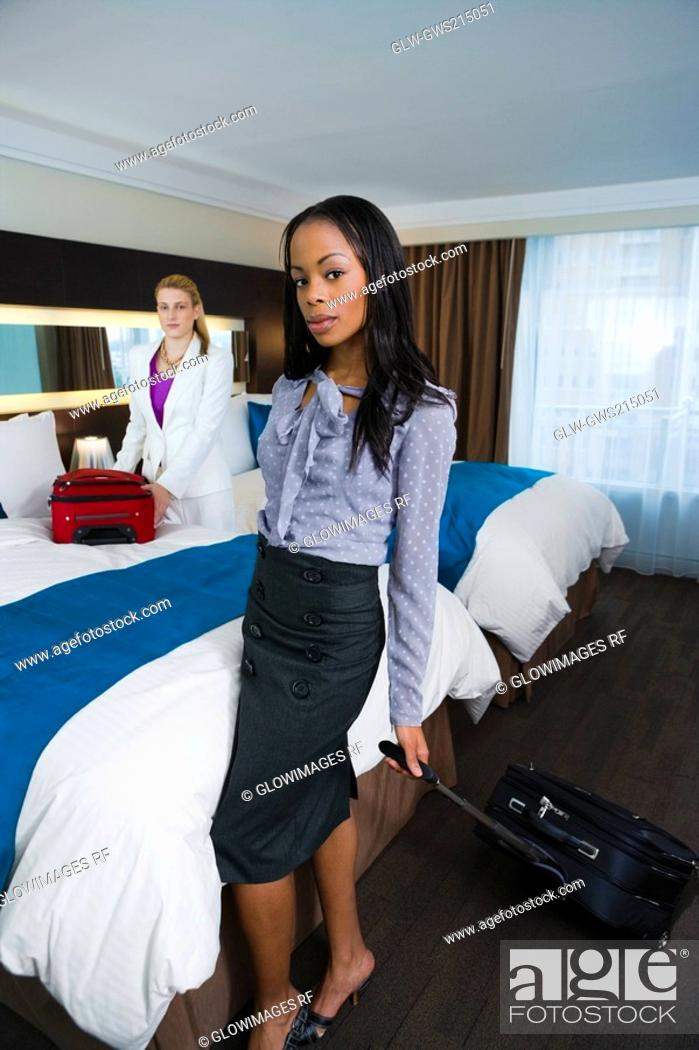 Stock Photo: Two businesswomen with their luggage in a hotel room.