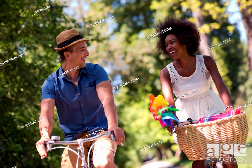 Stock Photo: a young man and a beautiful African American girl enjoying a bike ride in nature on a sunny summer day.