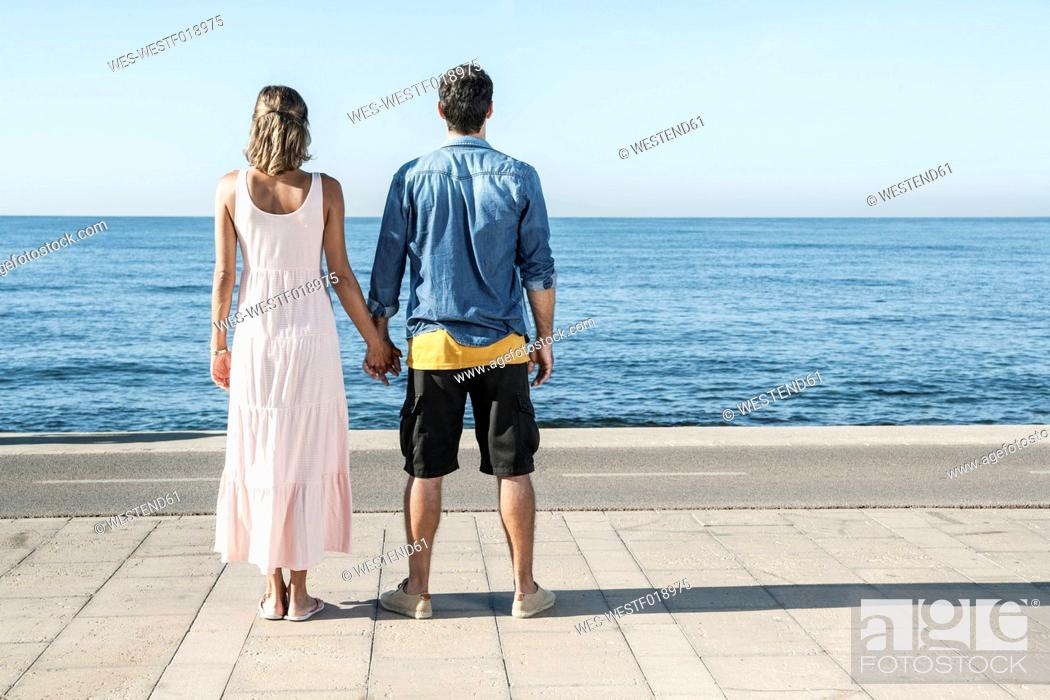 Stock Photo: Spain, Mid adult couple standing at Atlantic Ocean, looking at view.