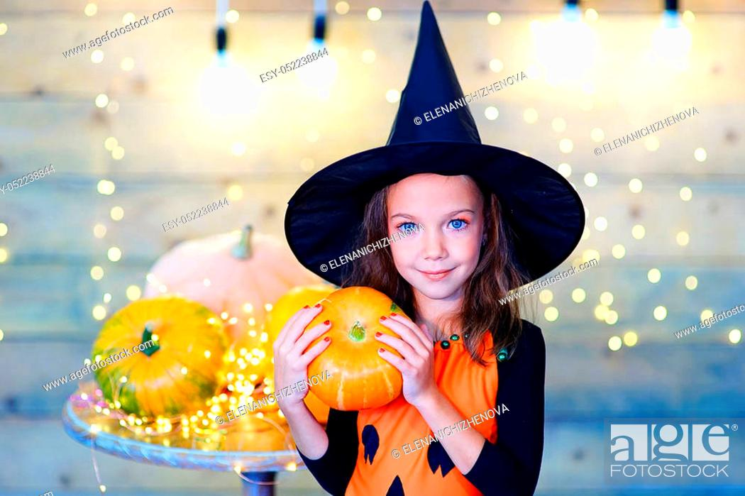 Stock Photo: Happy witch children during Halloween party playing around the table with pumpkins.