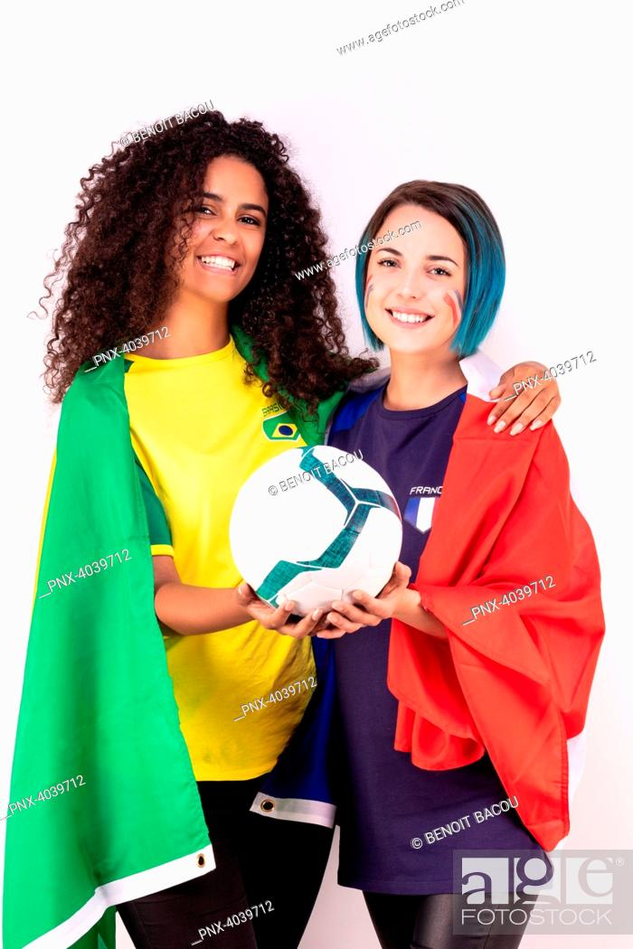 Stock Photo: Portrait of two young fans of the Brazilian team and the French fraternising team, a ball in their hands.