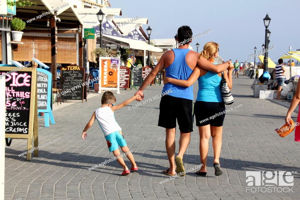 Stock Photo: family walking in the harbour area in parga greece.