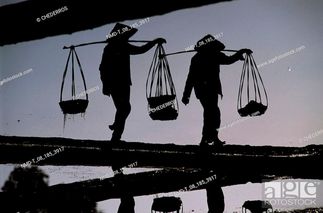 Stock Photo: Silhouette of two people carrying basket at dusk, Vietnam.