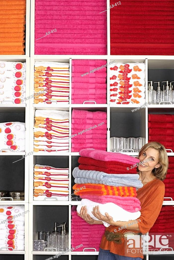 Stock Photo: Woman shopping in department store, holding large pile of towels beside shelf, smiling, portrait.