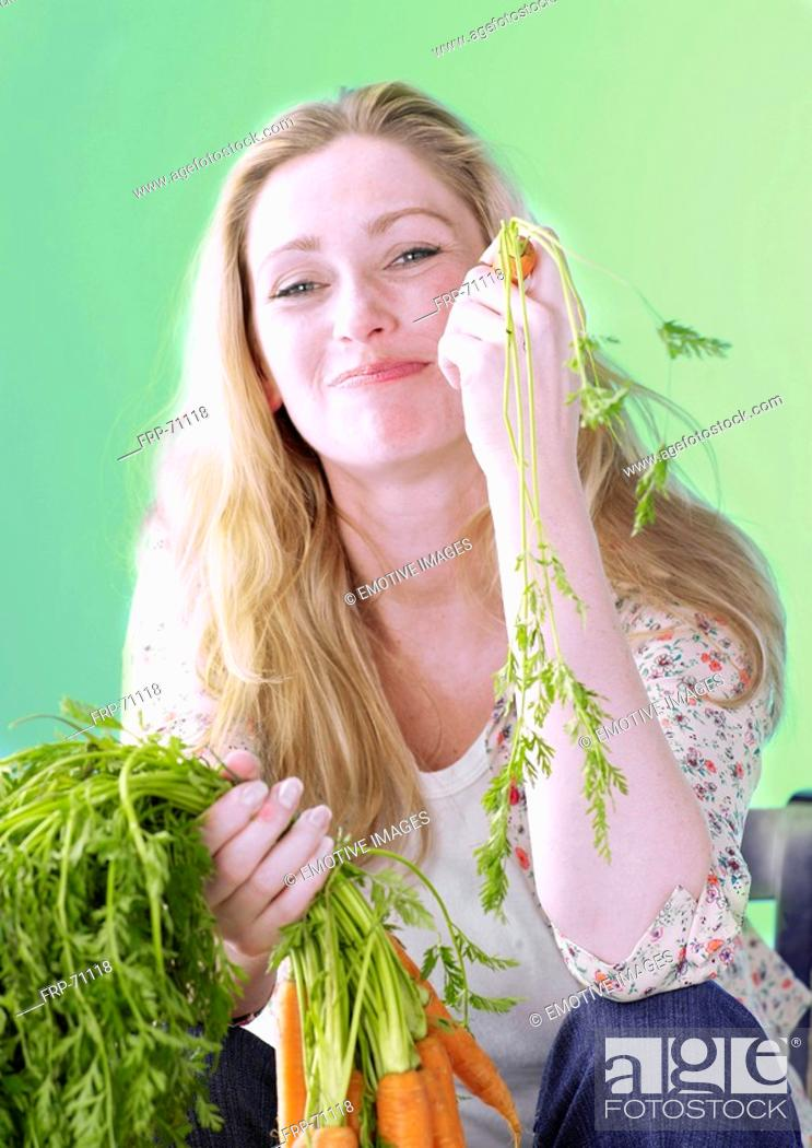 Stock Photo: Blonde woman with carrots.