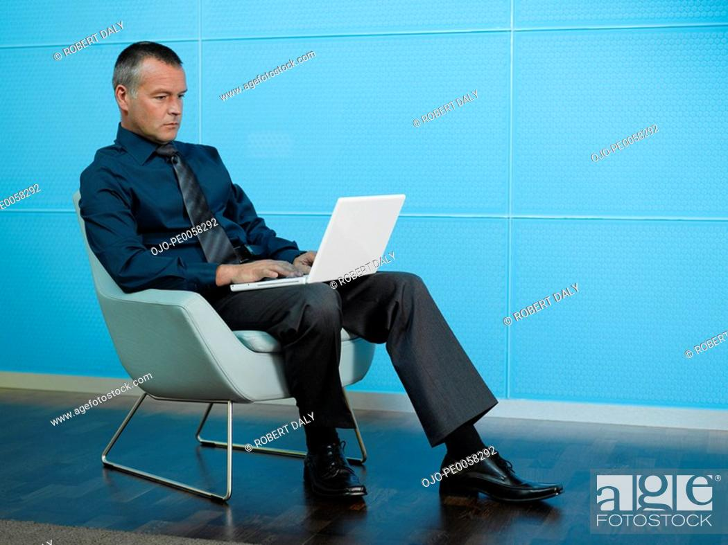Stock Photo: Businessman sitting with laptop in blue office.