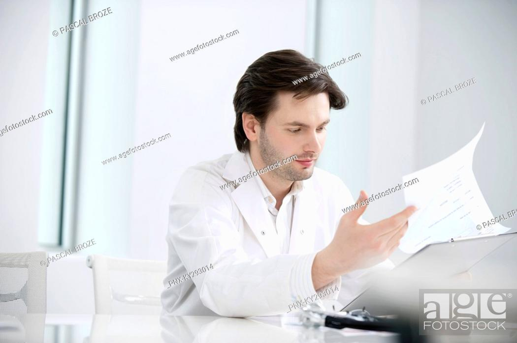 Stock Photo: Male doctor examining a medical report.