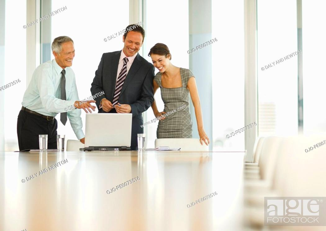 Stock Photo: Smiling business people looking at laptop in conference room.