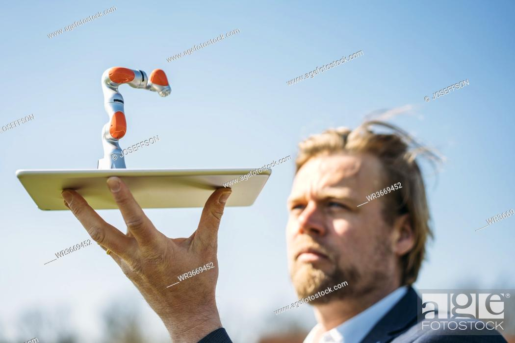 Stock Photo: Male professional holding at small robotic arm on digital tablet against clear sky.