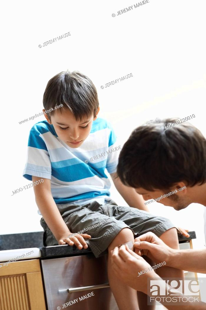 Stock Photo: Father Applying plaster to knee of son.