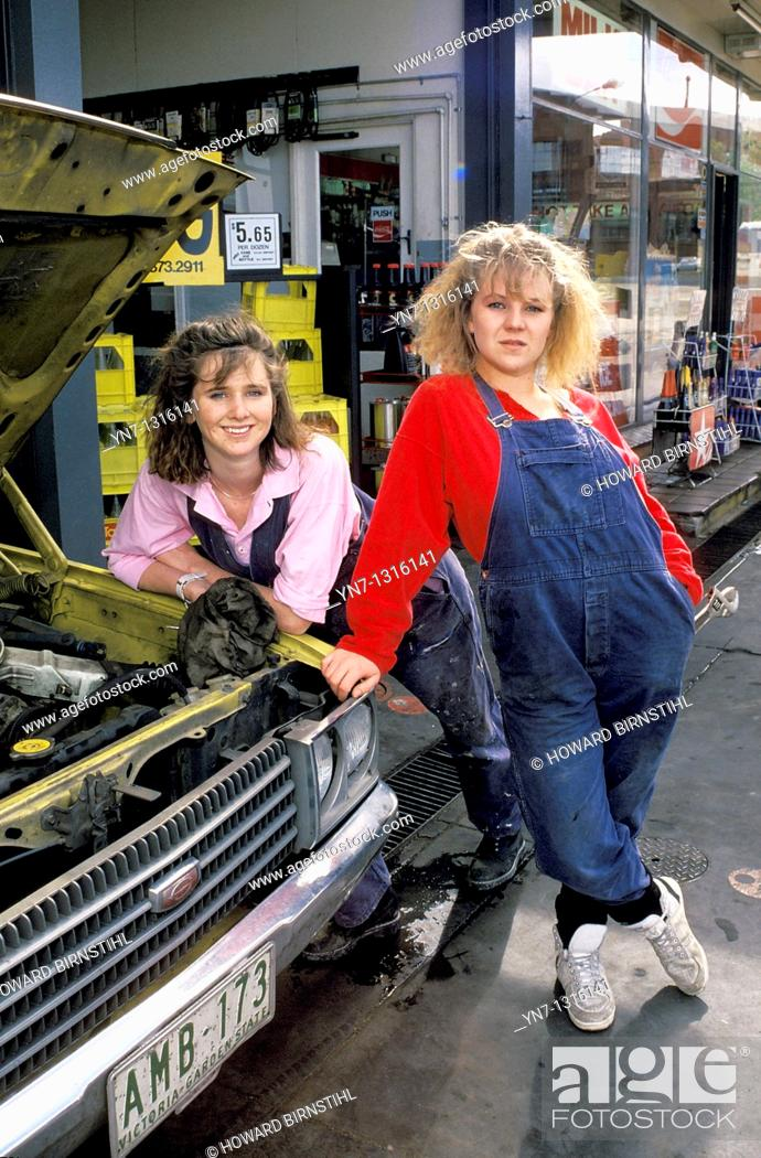 Stock Photo: two female mechanics outside their workshop posing for the camera.