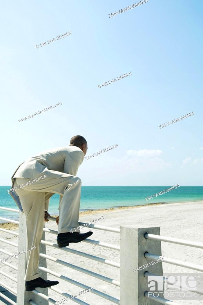 Stock Photo: Businessman climbing over fence at the beach, side view.