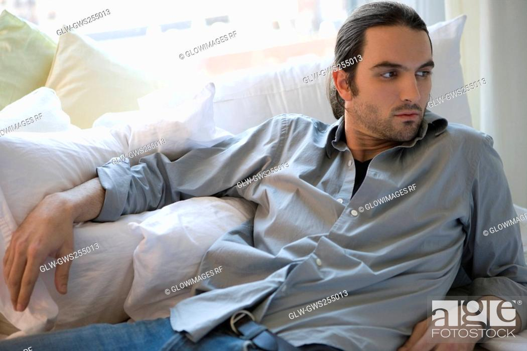 Stock Photo: Young man lying on the bed and thinking.