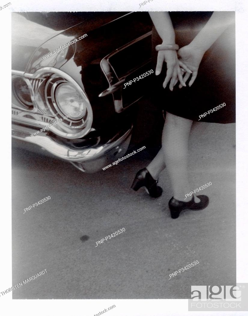 Stock Photo: Woman standing by a vintage car.