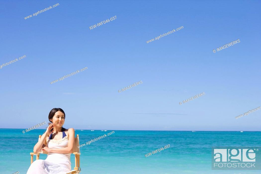 Stock Photo: A smiling young woman sitting on chair at beach.