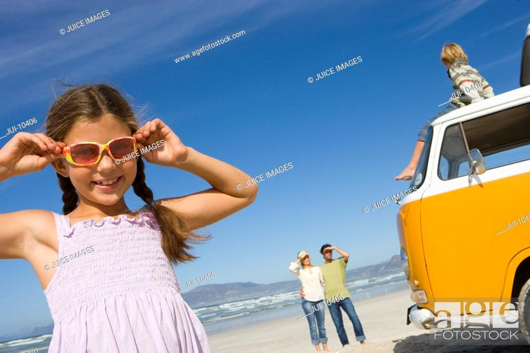 Stock Photo: Girl 5-7 in sunglasses by family and camper van on beach, smiling, low angle view.