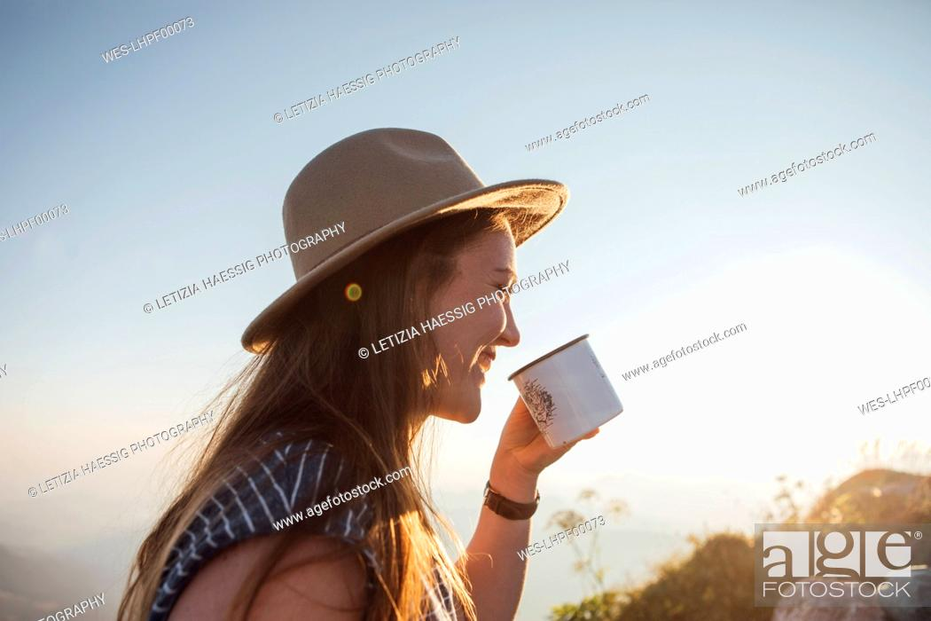 Stock Photo: Happy young woman on a hiking trip at sunrise holding a cup.