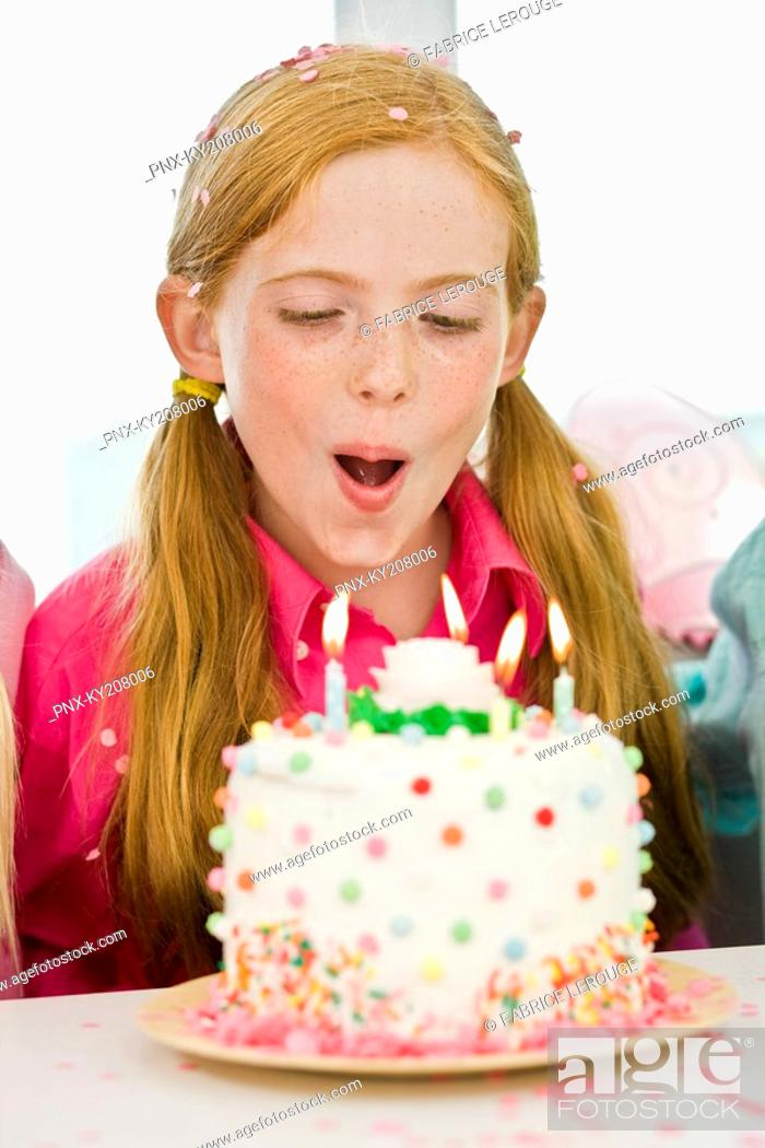 Stock Photo: Girl blowing out candles on a birthday cake.