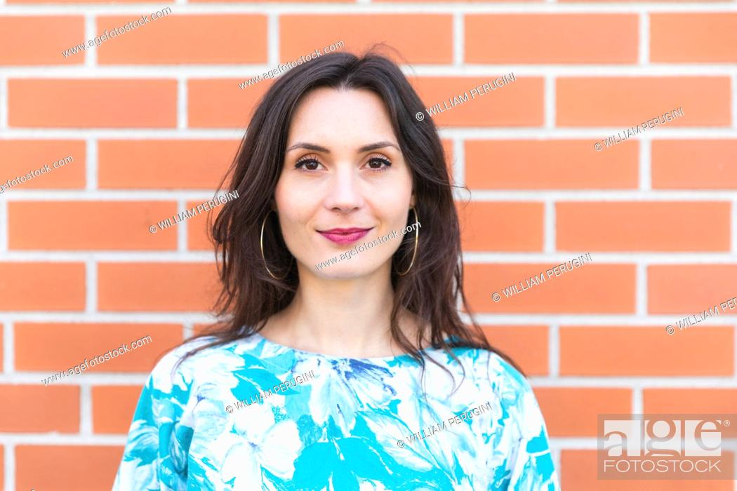 Stock Photo: Portrait of smiling young woman portrait against brick wall.
