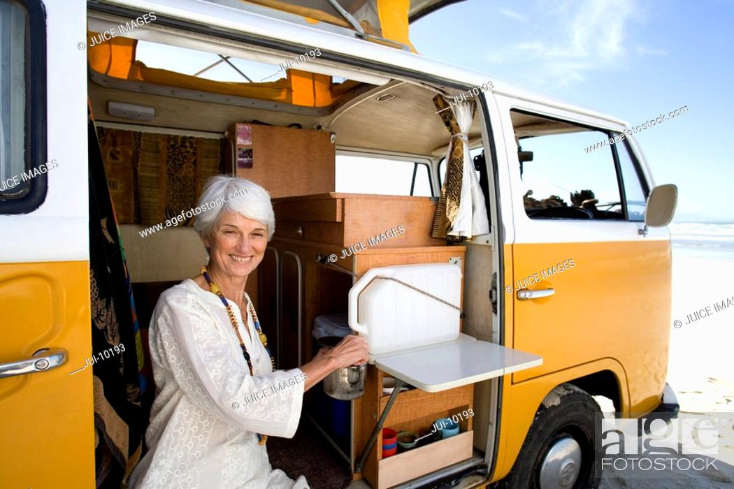 Stock Photo: Senior woman making tea in camper van on beach, smiling, portrait, close-up.