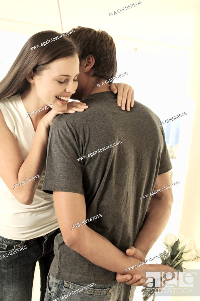 Stock Photo: Man hiding bunch of flowers behind his back, facing smiling woman.