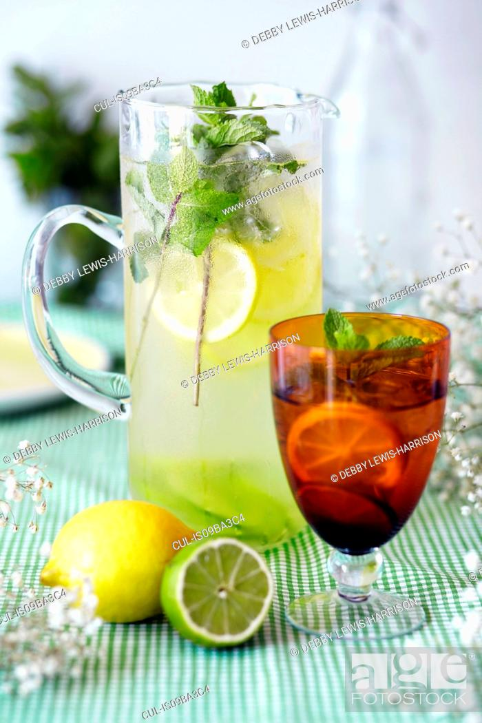 Stock Photo: Jug and glass of lemon and lime cordial, with fresh fruit and ice, close-up.