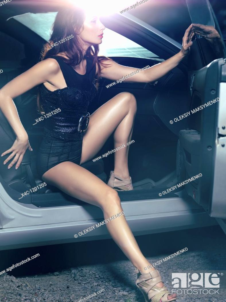 Stock Photo: Sexy young woman with beautiful long legs getting out of a luxury car  High fashion photo.