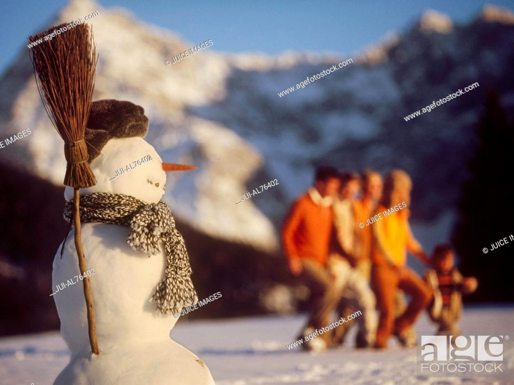 Imagen: Detail view of a snowman with a family in background.