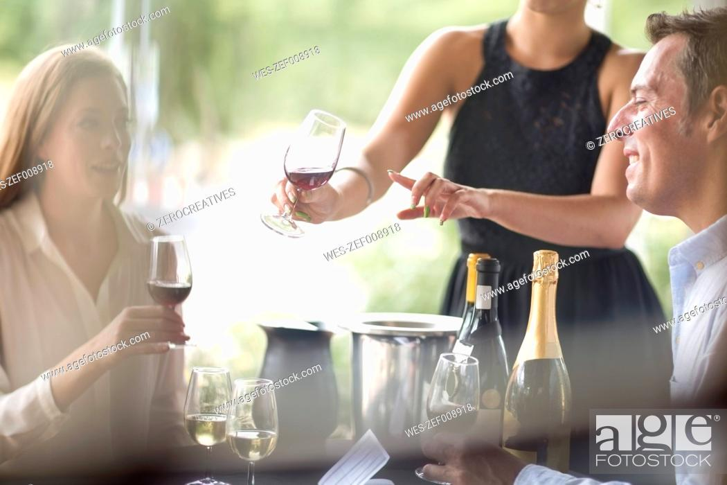 Stock Photo: Waitress in restaurant presenting red wine.