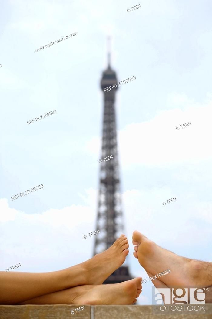 Stock Photo: Close up of young couples bare legs with Eiffel tower in background.