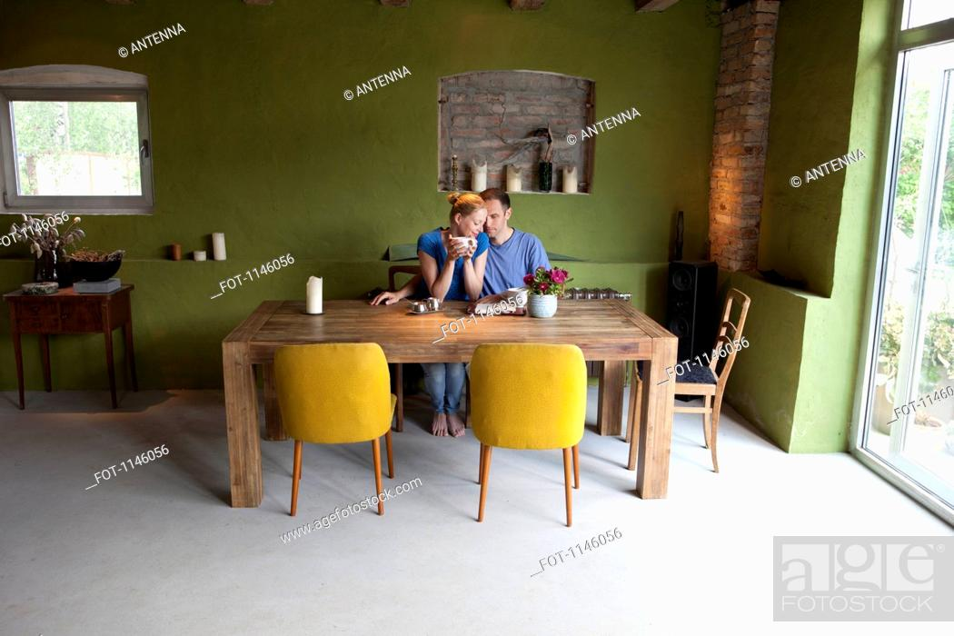 Stock Photo: An affectionate couple sitting at a table with a personal organizer and coffee.