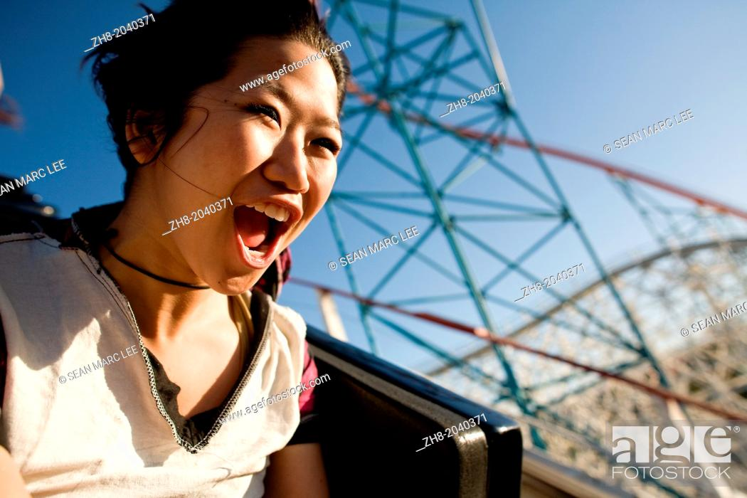 Stock Photo: A young woman screams as she rides down a roller coaster in Southern California theme park.