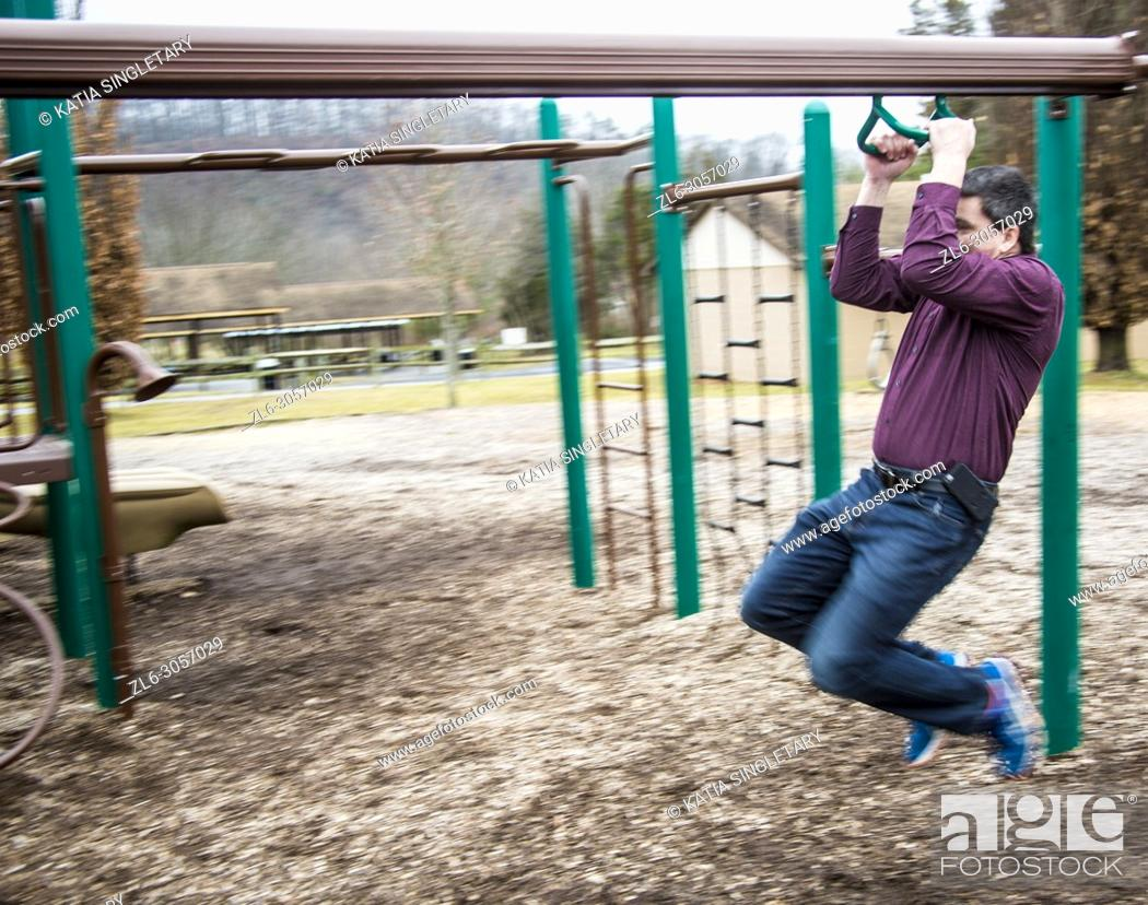 Stock Photo: Caucasian handsome dark hair man wearing a purple shirt and his bluetooth. He is in playing in kids playground and going down the Zipline.