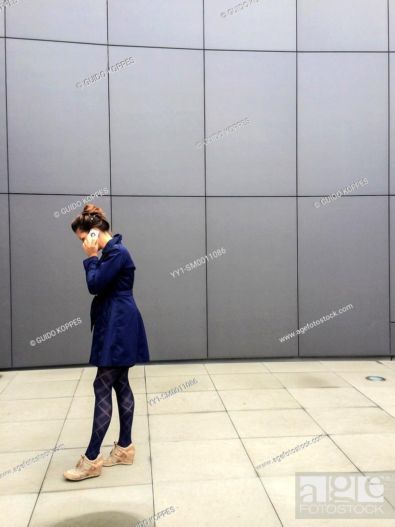 Stock Photo: Breda, Netherlands. Young, attractive woman having a conversation through her smart phone, while walking up and down a courtyard.