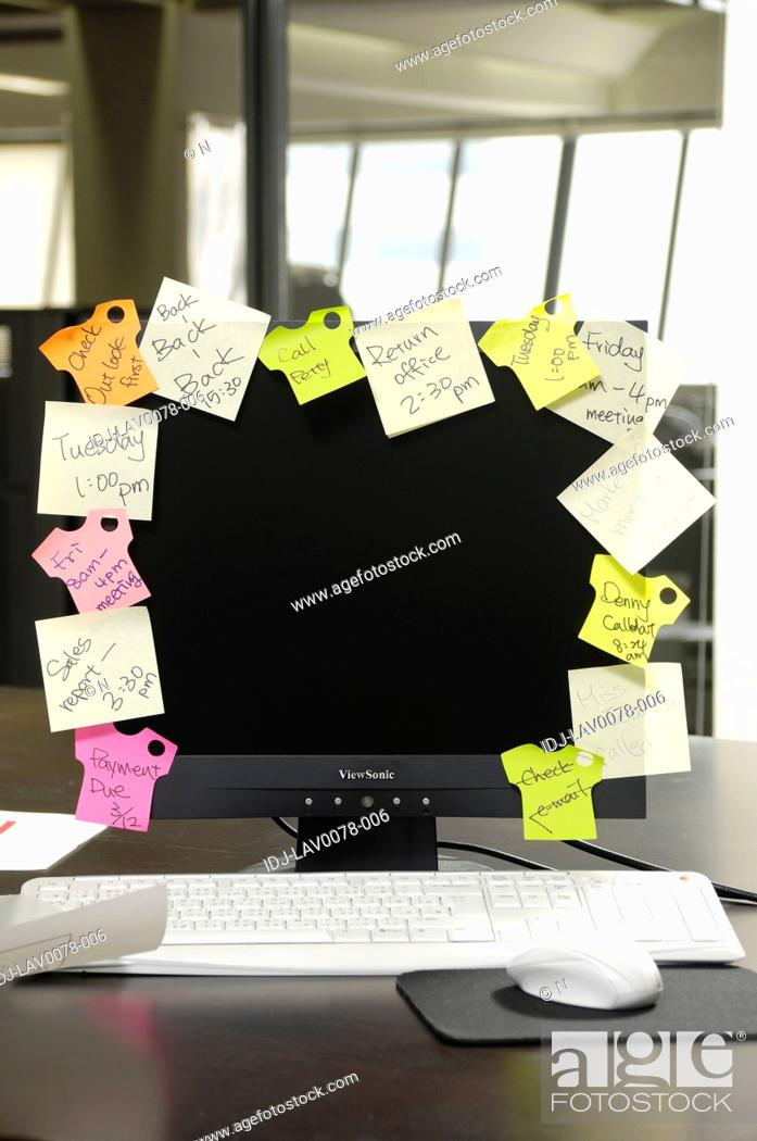 Stock Photo: Adhesive notes stuck on a computer.