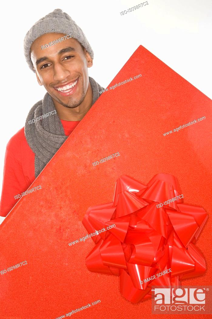 Stock Photo: Man holding a large red gift.