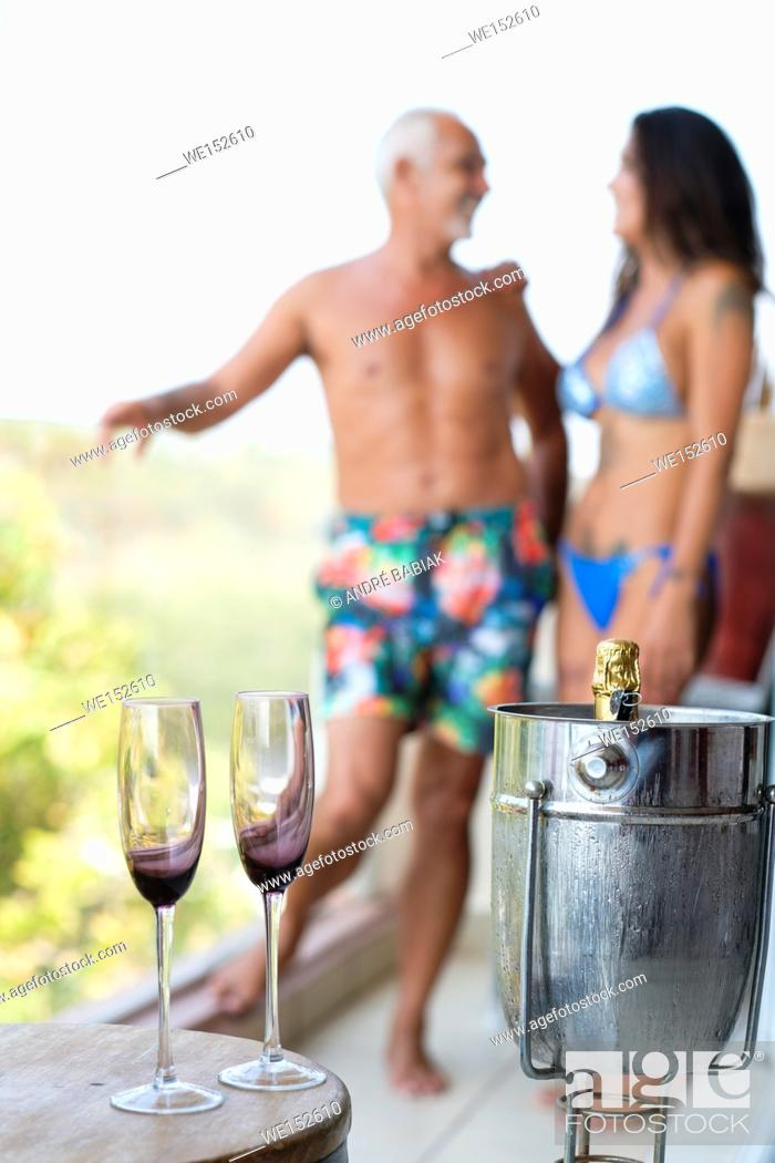 Stock Photo: Man and woman in swimwear with champagne glasses and bottle in a cooler on a balcony.