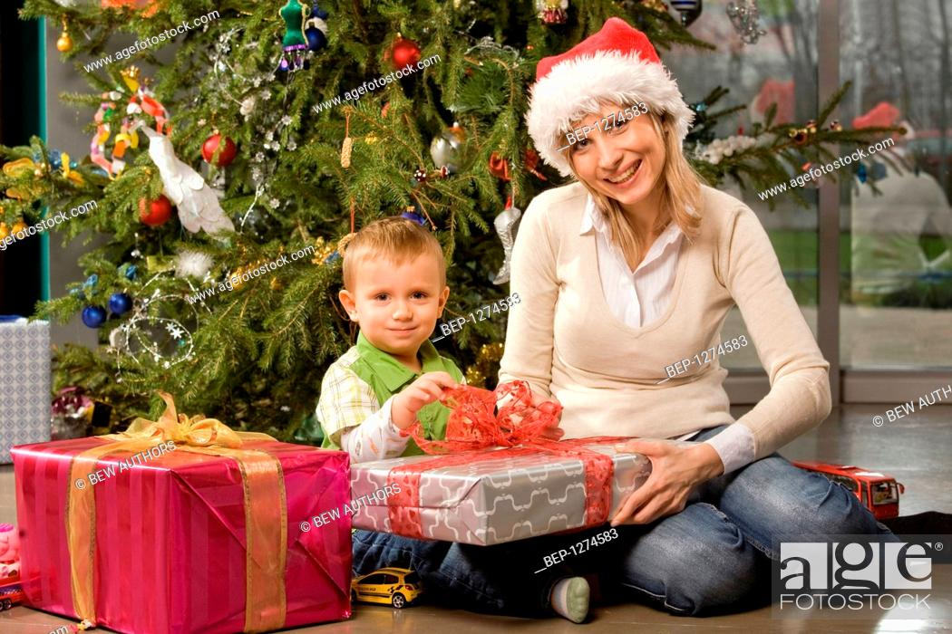 stock photo woman opening christmas presents with her son