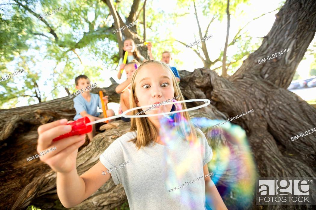 Stock Photo: Caucasian girl making bubbles.