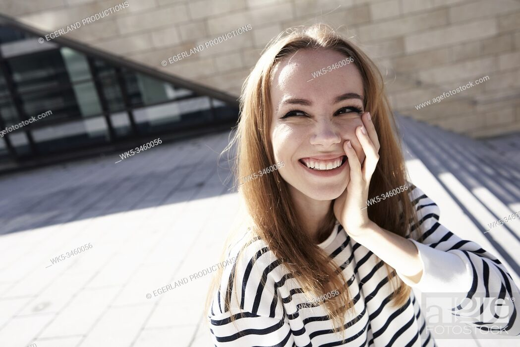 Stock Photo: Portrait of young woman with hand on cheek. Munich, Germany.