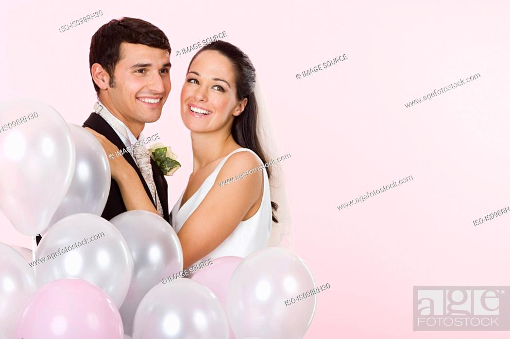 Stock Photo: Bride and groom with a bunch of balloons.