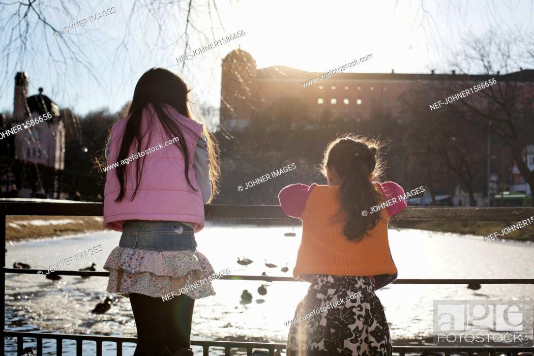 Imagen: Girls looking at ducks in park.