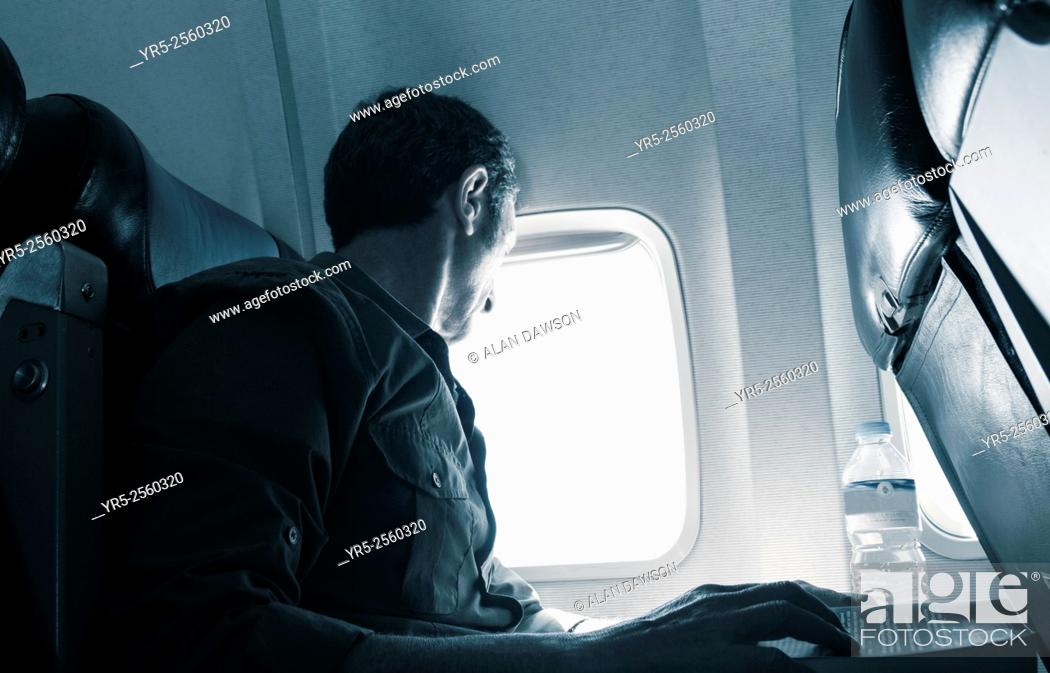 Stock Photo: Mature man looking out of airplane window.
