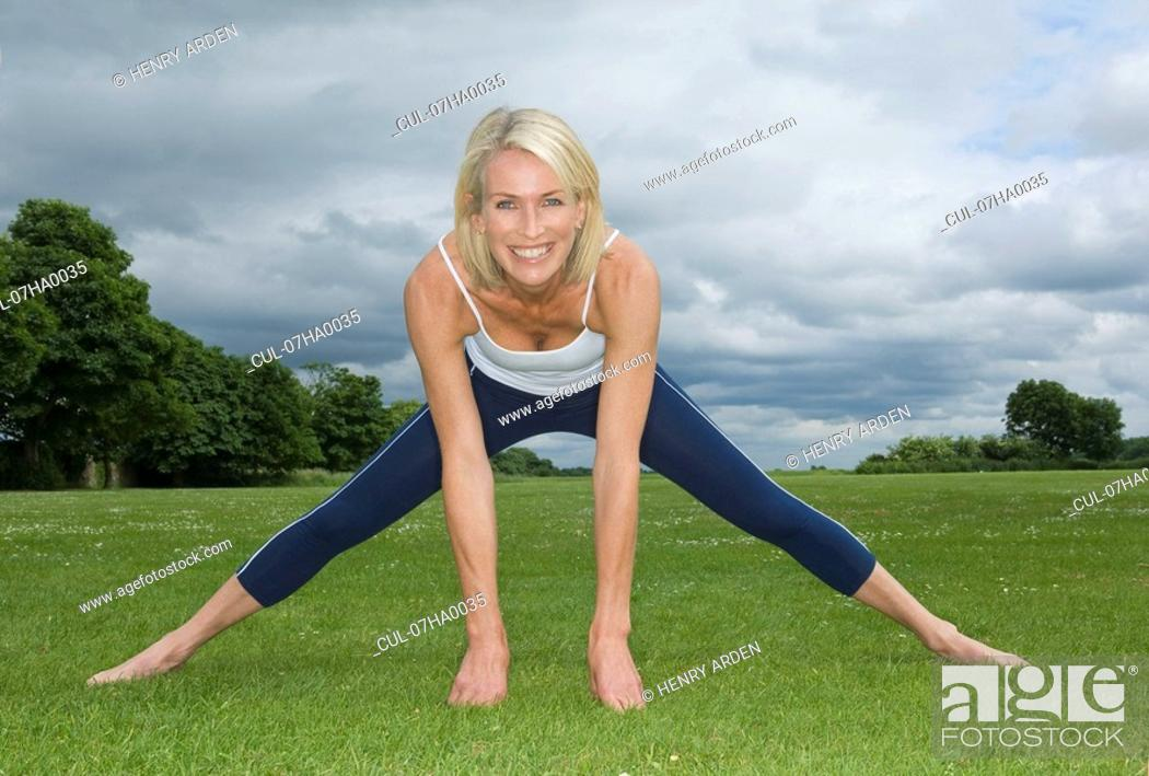 Stock Photo: Smiling woman in park exercising.