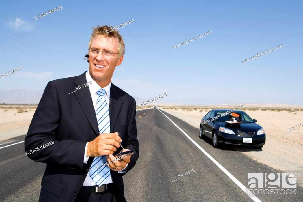 Stock Photo: Businessman in middle of open road in desert, using electronic organiser by car.