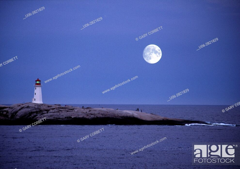 Stock Photo: large moon over peggy's cove lighthouse in nova scotia.