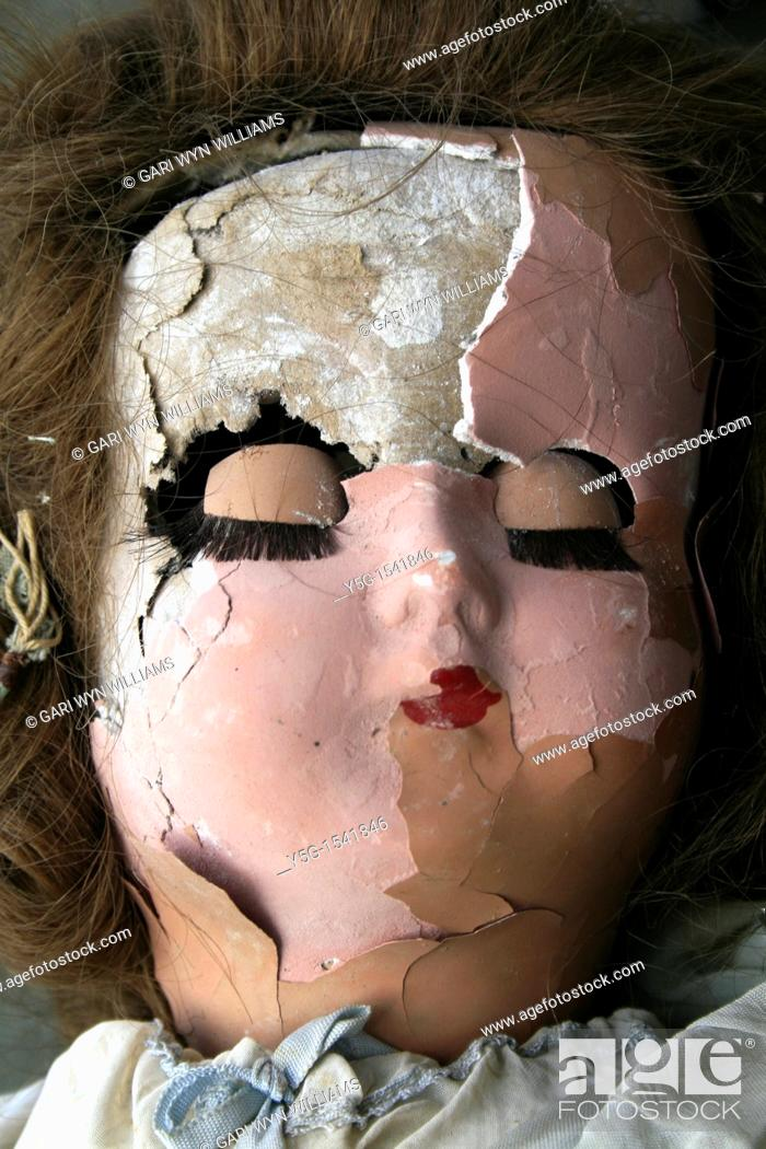 Stock Photo: old dirty damaged girl doll head in window.