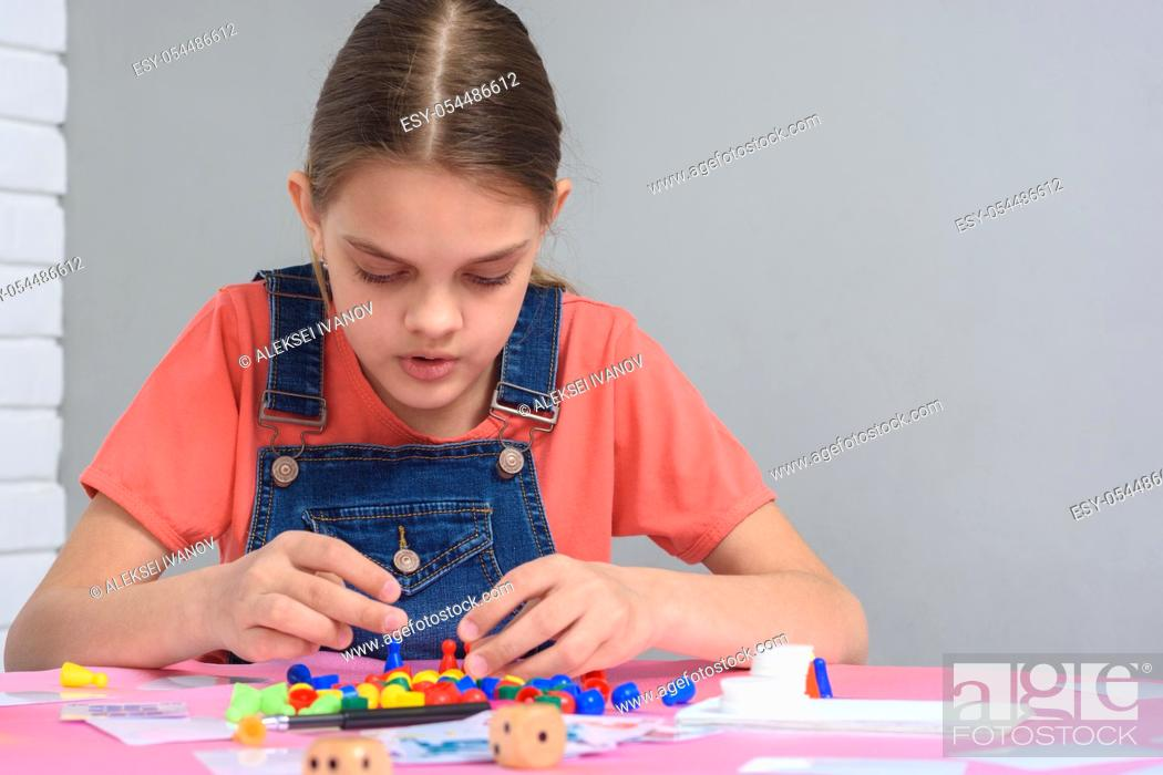 Stock Photo: Girl enthusiastically plays board games.