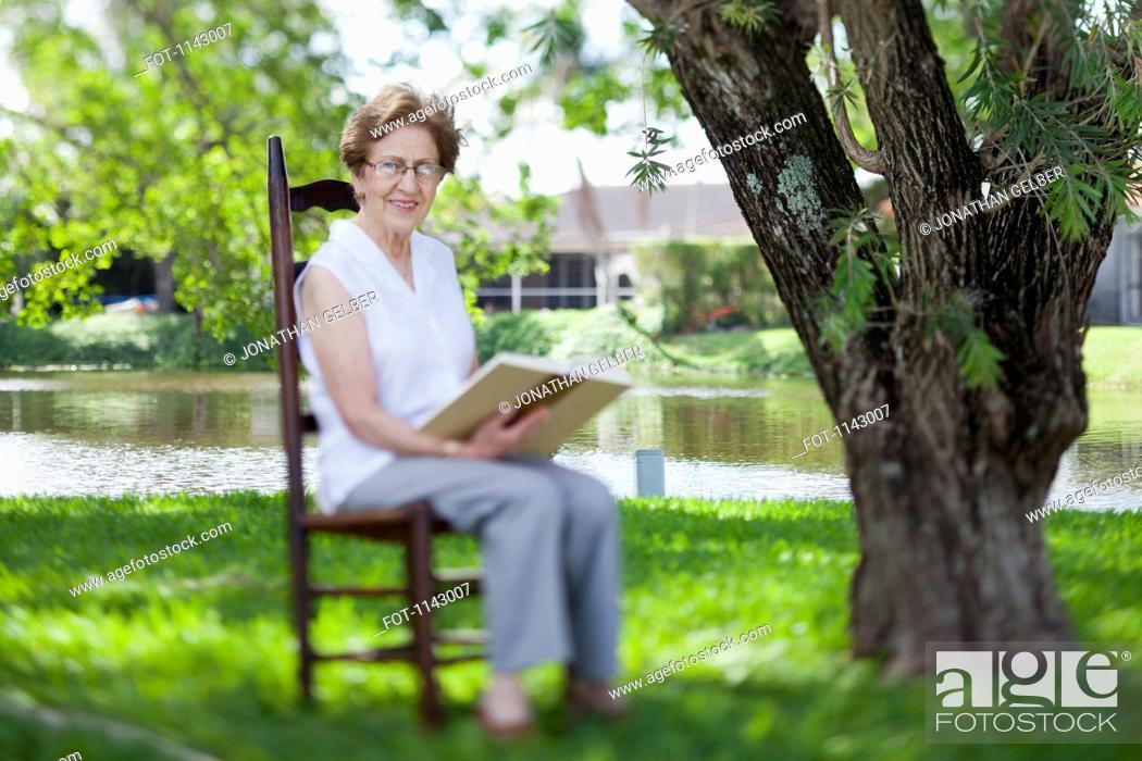 Stock Photo: A senior woman reading next to a river.