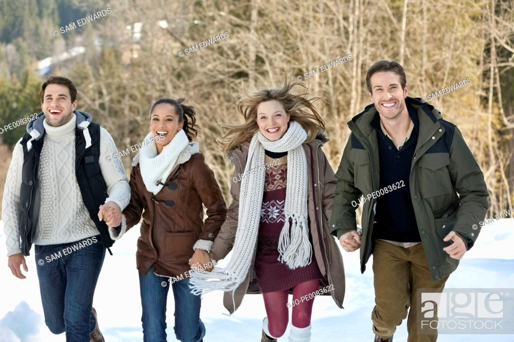 Stock Photo: Portrait of smiling friends holding hands and running in snow.